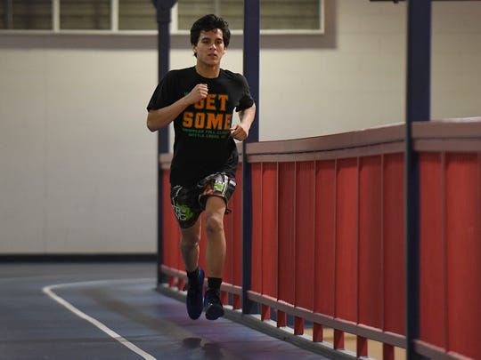 Wrestling practices entail much more than matchups on the mat. Here, Nathan Atienza runs some laps on the track during practice at Livonia Franklin.
