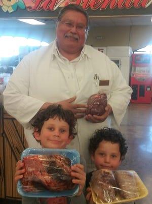 La Tienda meat department manager Adam Quintero posed with students Aron Marancenbaum, left, and Asher Marancenbaum and cow tongues and kidneys.