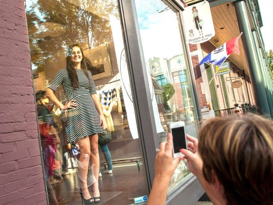 Carly Knapp poses for a picture while working as a living mannequin inside of Elizabeth & West Fashion House during Boutique Week last year.