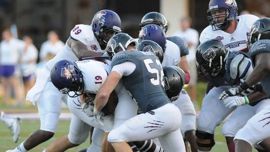 Andrew Beisel helps haul down a Northwestern State ballcarrier Thursday night.