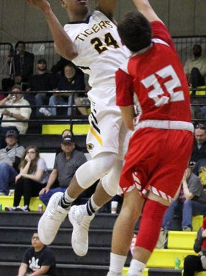 Alamogordo's Chamar Norman, left, puts up a shot while being guarded by Valencia's Daniel Calderon on Saturday evening at the Tiger Pit.