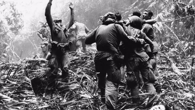 As soldiers aid wounded buddies, a paratrooper of A Company, 101st Airborne, guides a medical evacuation helicopter through the jungle foliage to pick up casualties during a five-day patrol of Hue, South Vietnam, in April 1968.