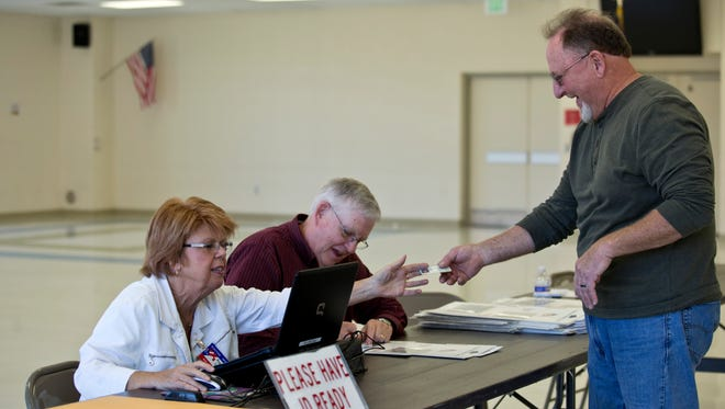 Election Officials Annette Duffy and Bob Sheehy prepare a ballot for David Barber, a current city councilman, Tuesday, November 3, 2015 at Marysville Middle School.