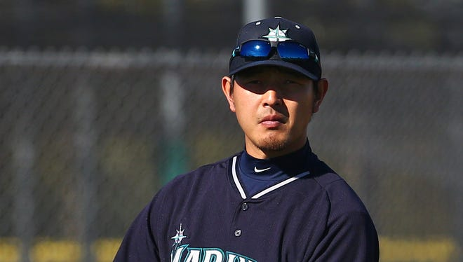 Seattle Mariners injured pitcher Hisashi Iwakuma wears a cast on his finger during team workouts.