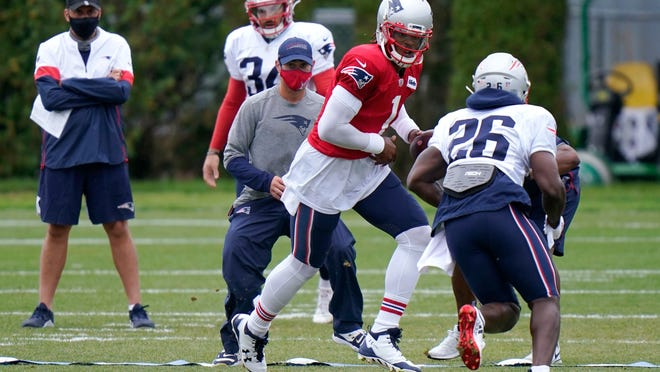 Patriots quarterback Cam Newton hands off to running back Sony Michel during a training camp practice in late August.