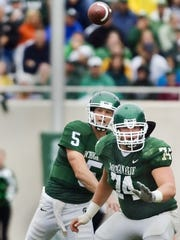 MSU quarterback Drew Stanton (left) passes while being