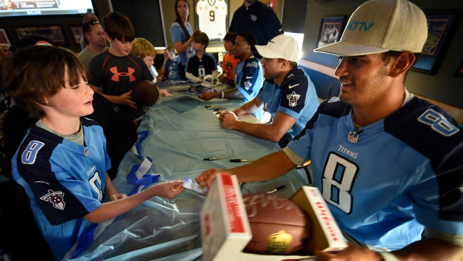 Titans quarterback Marcus Mariota signs an autograph for Hayden Smith at a Titans Caravan event Wednesday May 4, 2016, in Florence, Alabama.