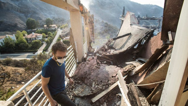 Shane Clark lost his home, still smoldering, in the Bell Canyon neighborhood during the Woolsey Fire in Southern California. He walks in what was once his deck overlooking a canyon.