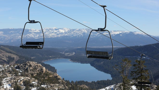 In this photo taken Wednesday, Jan. 28, 2015, chairs on a ski lift overlooking Donner Lake, sit idle at Donner Ski Ranch in Norden, Calif.  The ranch is one of several ski resorts that have either suspended operations or cut back on the number of lifts operating due to the state's historic drought.