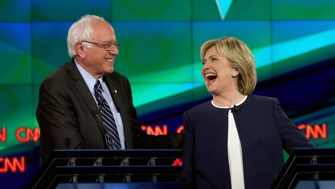 Sen. Bernie Sanders (I-VT) (L) and former Secretary of State Hillary Clinton share a light moment during the first Democratic presidential debate on Oct. 13, 2015 at Wynn Las Vegas.