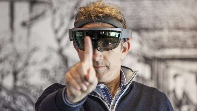 "USA TODAY tech reporter Marco della Cava uses a finger to ""air touch"" an action while using Microsoft HoloLens, one of the first extended sessions with the device that the company has granted."
