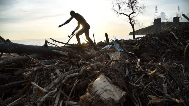 A man collects debris from a destroyed house in the small village of Labey in southwest of Haiti on Oct. 11.
