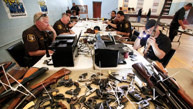 Sheriff's officers enter into a database guns people relinquished in 2013 in Detroit.