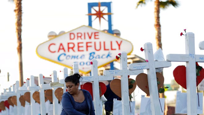Cece Navarrette sits near a cross for her cousin, Bailey Schweitzer, who was among those killed during the mass shooting Friday, Oct. 6, 2017, in Las Vegas.