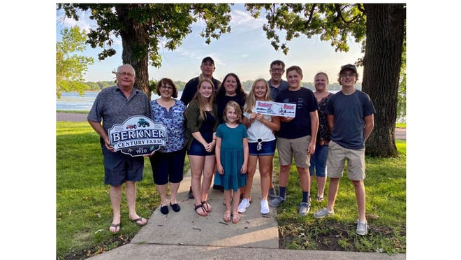 THREE GENERATIONS OF the Berkner family attended the Century Farm recognition event on Aug. 13.  Front:  Dan's daughter Anna. Second row, from left: Brad (holding the custom sign his sons had made) and Leann; Bryan's family, Julia, Mindy, and Taylor; Dan's sons Sam and Alex. Back row: Bryan, Dan and Krista.