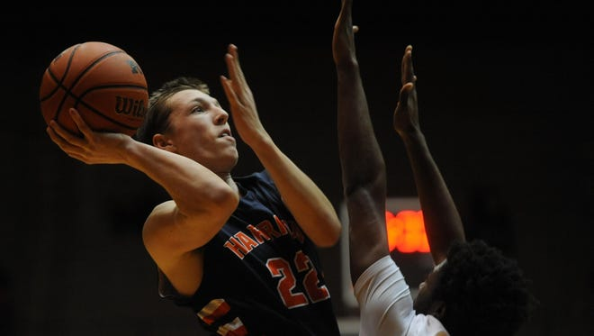 Harrison's Jakub Hall goes for a shot over Richmond's Adrion Gibson during Friday night's basketball game at Tiernan Center.