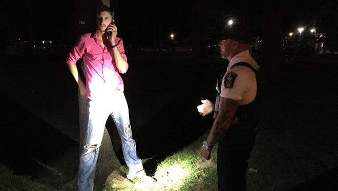Lt. Doug Miller of the Put-in-Bay Police Department arrests a New London man for disorderly conduct-intoxicated after he was found slumped against a tree in DeRivera Park in downtown Put-in-Bay.
