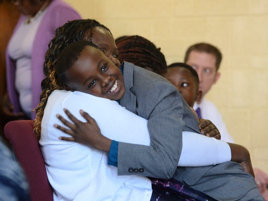 "A boy hugs Joan Namachemo, the wife of Matanda ""Mike"" Wasike, who died after nearly five years of trying to recover from a beating, during a service memorializing his life Saturday at Imani Family Church in West Des Moines."
