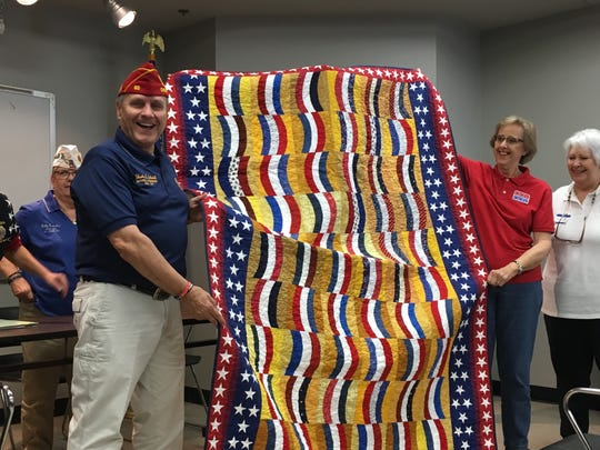 American Legion Commander Charles Schmidt accepts a Quilt of Valor from members of the Ozark Piecemakers Quilt Guild following his address to members of American Legion Post 1214 Wednesday, Nov. 2 in Springfield.