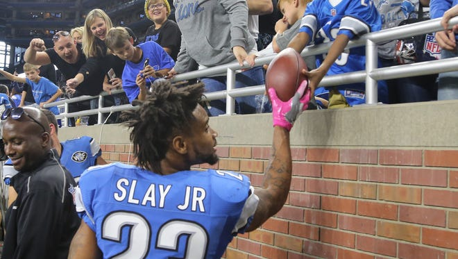 Detroit Lions cornerback Darius Slay gives the game ball to his son after the 24-23 win over the Eagles on Sunday, October 9, 2016 at Ford Field in Detroit.