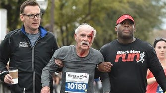 "Flanked by a fellow runner and a spectator, John Wilkie continues toward the half-marathon finish line. ""These two guys just fell out the sky like angels and picked me up,"" he says."