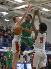 Novi's Jiovanni Miles drives between Canton's Chase Meredith (left) and Eian Barker.