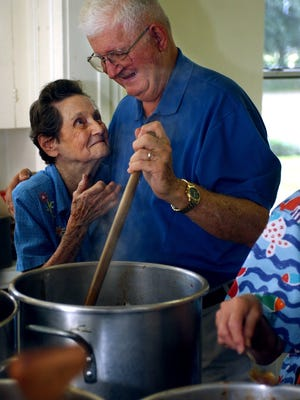 Mary Louise Williams, 87, and Walter Pierron, 71, laugh together over a pot of gumbo at Memorial United Methodist Church in Monroe Wednesday, Oct. 27, 2004.