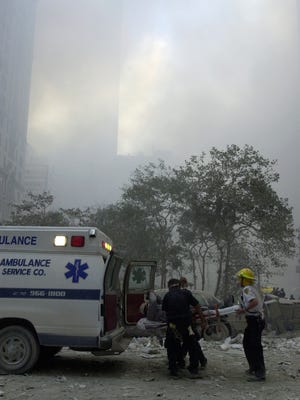 In this Sept. 11, 2001, photo, a man is lifted by stretcher into an ambulance following the collapse of both World Trade Center towers.