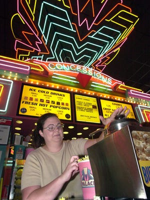 "A 2000 photo in which then-Palace Theatre manager Carrie Davison worked the concession stand. The theater announced Wednesday it will change its name to the Premiere Palace and show ""first-run discount"" movies."