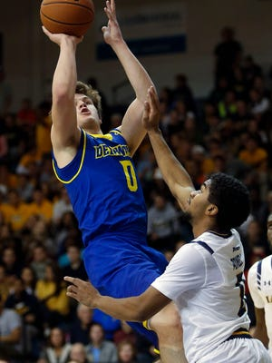Delaware guard Ryan Daly scores over LaSalle's Pookie Powell in the second half in Philadelphia Tuesday. The basket pulled Delaware within 59-58 with five minutes to play, but Delaware never took the lead the rest of the way in the 74-68 loss.
