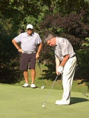 Wes Allred watches as Frank Thacker rolls in a 4-foot