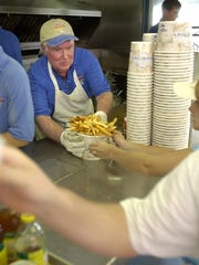 In this file photo, reporter John Purnell hands a sizzling cup of fries to hungry customers at the Thrasher's pier location.