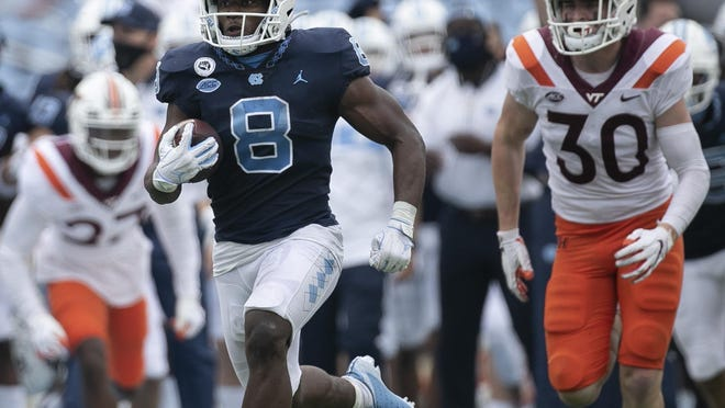 North Carolina running back Michael Carter breaks away from Virginia Tech defensive back Tyler Matheny, right, during the fourth quarter of last week's game to help clinch victory for the Tar Heels.