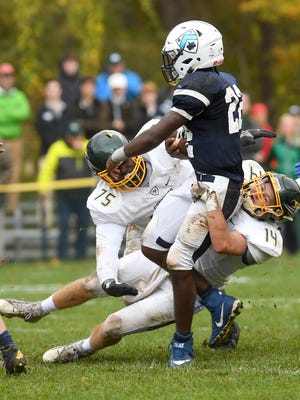 Christ School's Saevion Gibbs and West Shuler wrap up Asheville School's Uchenna Ikwuakor during the 91st meeting of the rival schools at Asheville School on Saturday, Oct. 28, 2017. The Greenies defeated the Blues 47-6.