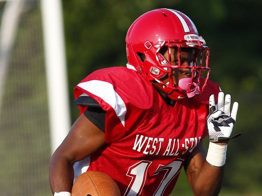 West's Tyron Harper runs back the opening kickoff during the East-West All-Star Football game at Kings High School Thursday.