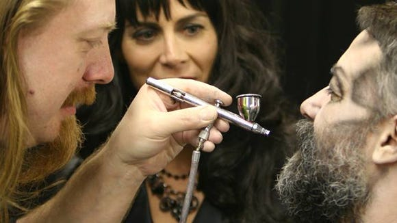 Makeup artist Chris Hanson, left, applies makeup to an actor at Rocky Point Haunted House.