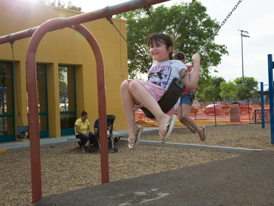 Sayra Machuca, 9, swings with her sister Sorayma at