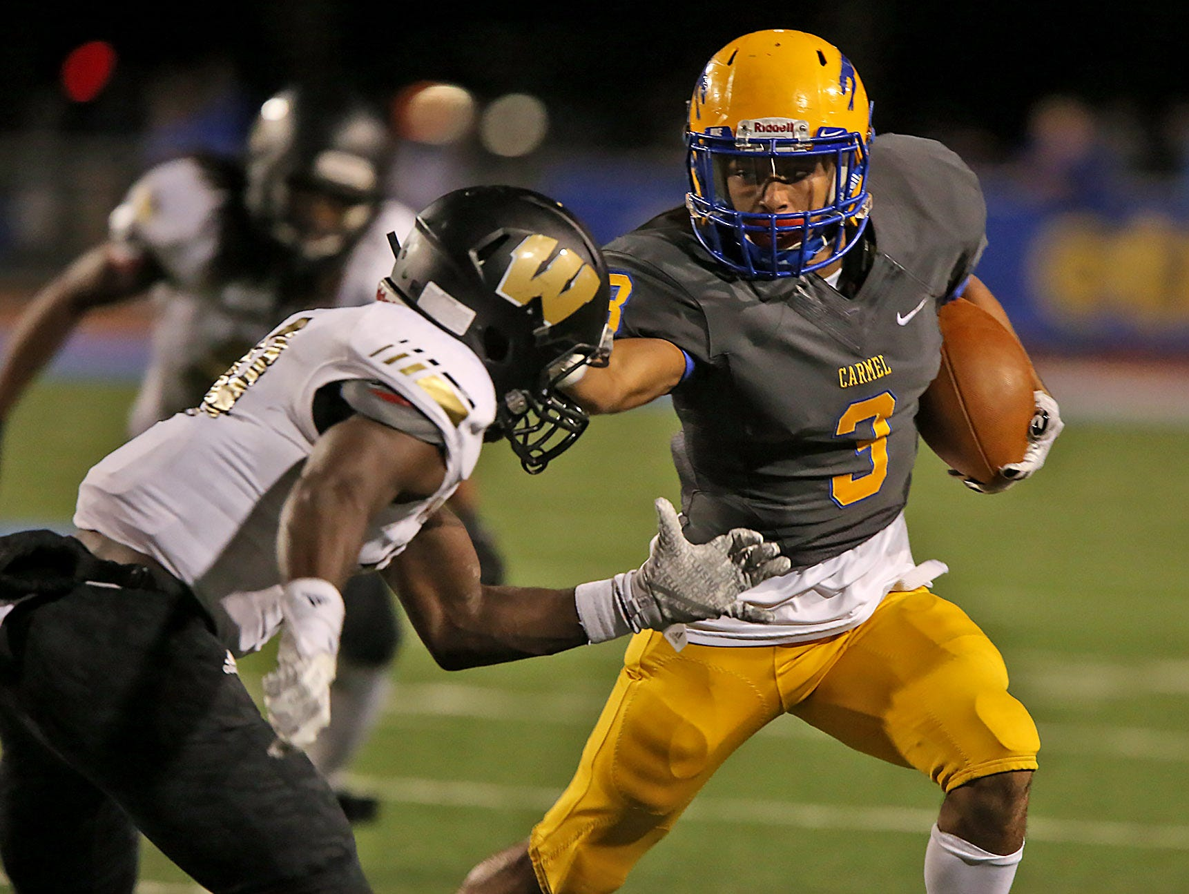 Carmel's Jalen Walker makes a run as Warren Central's Darien Rivers tries to stop him Oct. 9, 2015. The junior wide receiver committed to the University of Cincinnati.
