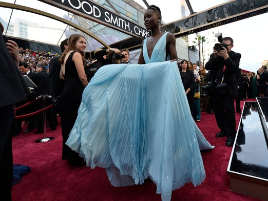 <p>Lupita Nyong'o arrives in the rain, well before her winning moment as best supporting actress for '12 Years a Slave.' Backstage, Nyong'o and Jared Leto (best supporting actor for 'Dallas Buyers Club') introduced each other to their respective brothers.</p>