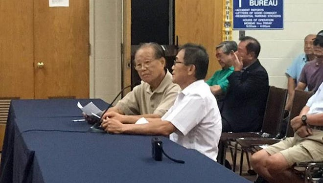 Hyukman Kwon, right, with interpreter James Chung, at a Palisades Park council meeting on Aug. 8.