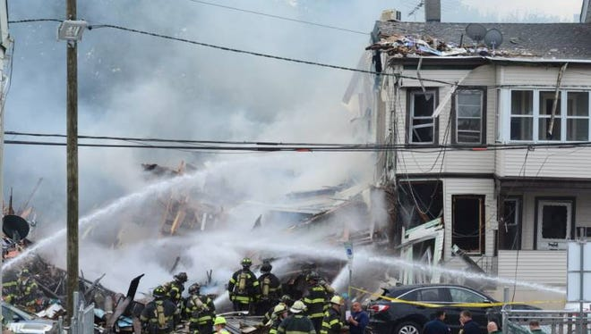 Firefighters continue to pour water at the site of the blast on Tuesday in Paterson.