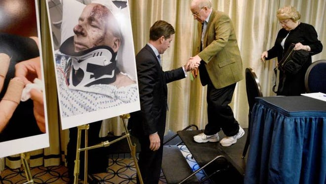 Sheldon Kest, with his wife, Lynda Kest, is helped from the stage by attorney Andrew R. Duffy as he leaves a press conference Tuesday.