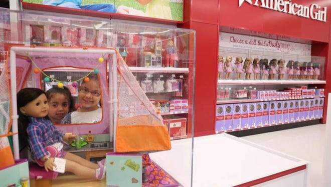Alyssa Baez, 5,  (left) with her sister, 7-year old Hailey Baez look over the display of American Girl dolls at the Totowa Toys 'R' Us.