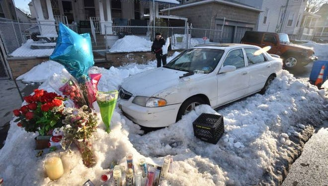 Flowers and candles were seen in front of a white Mazda where a mother and her two children died, parked along Sherman Street in Passaic on Wednesday, Jan. 27, 2016.