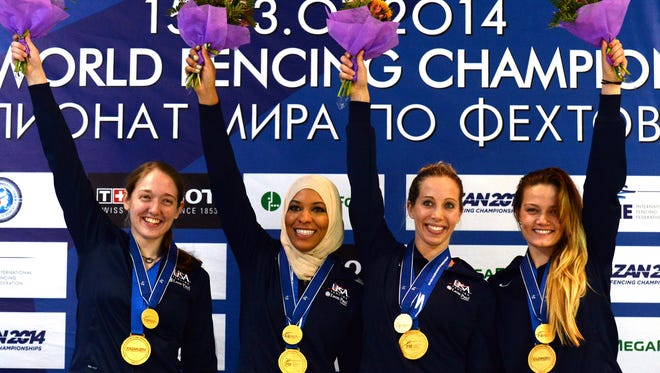 (From left) Anne-Elisabeth Stone, Ibtihaj Muhammad, Mariel Zagunis and Dagmara Wozniak of the United States team celebrate with their medals on the podium after winning the women's team sabre final at the 2014 World Fencing Championships in Russia.