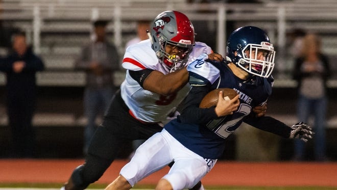 Atlantic City quarterback Michael Constabile (12) is sacked by Vineland outside linebacker Nihym Anderson (8) at Atlantic City on Friday, October 20.