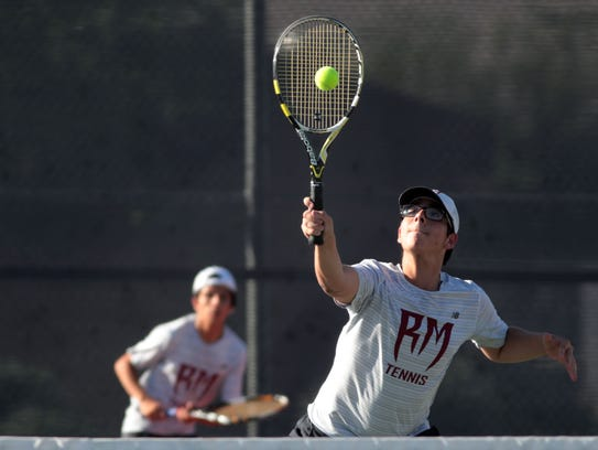 Rancho Mirage's Carlos Arias volleys as his partner