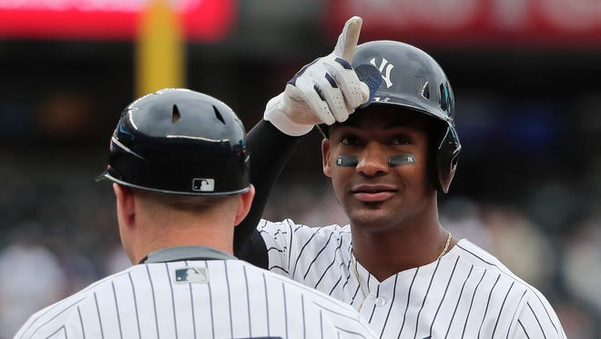 New York Yankees' Miguel Andujar motions the crowd after driving in a run against the Oakland Athletics during the fifth inning of a baseball game, Saturday, May 12, 2018, in New York.