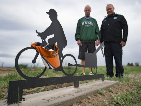 Mark and David Jacoby, brothers of John Jacoby, pose for a portrait at a roadside memorial on Weld County Road 15 in Windsor on May 10. John Jacoby was murdered while riding his bicycle along the same road in May 2015.