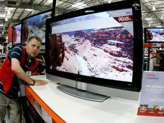 A Costco employee makes an adjustent on a high-definition television at a store in Tacoma, Wash.
